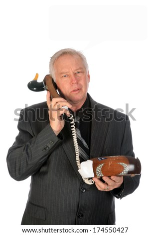 A handsome and obviously well educated business man tries to hold a serious conversation but runs afoul while on a Duck Decoy Telephone. Isolated on white with room for your text. - stock photo