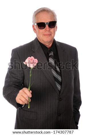 A Handsome and Romantic Business Man in a Grey Pin Stripe Suit holds a Pink Carnation and a Red Heart Shaped box of Chocolates for Valentines Day or any Special Occasion. Isolated on white. - stock photo