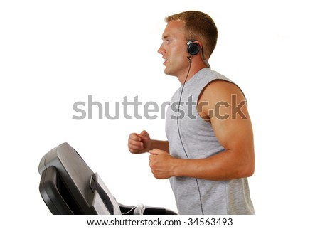 A handsome athletic man running on a treadmill - slight motion blur on arms - stock photo