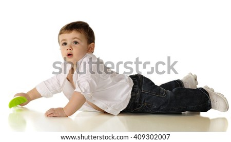 A handsome baby boy on his belly, propped up to see what's going on.  Isolated on white. - stock photo