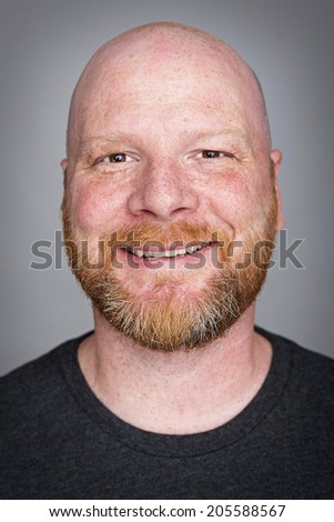 A handsome bald man with a red haired beard and a smile - stock photo