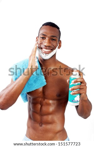 A handsome black man, holding a can of shaving cream, with shaving cream applied to his face. - stock photo