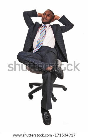 A handsome black man sitting on a chair, his legs crossed and leaning back and relaxing for white background.  - stock photo