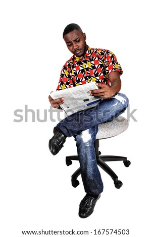 A handsome black man sitting on a chair, his legs crossed and reading the news paper for white background.  - stock photo
