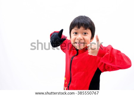 A handsome boy showing his thumbs while smiling in front of white background. - stock photo