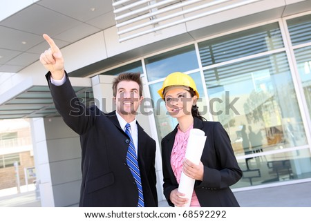 A handsome business man and woman construction team at office building - stock photo