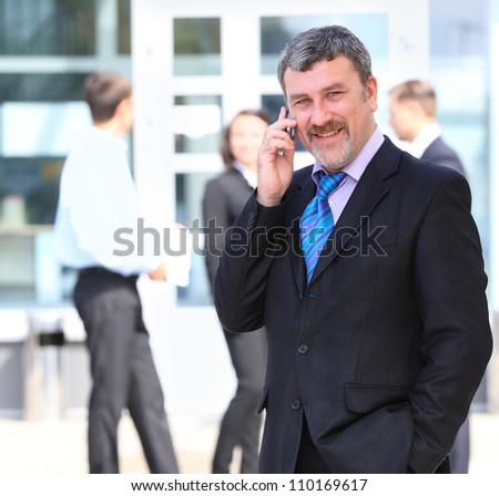 A handsome business man on phone at office building - stock photo