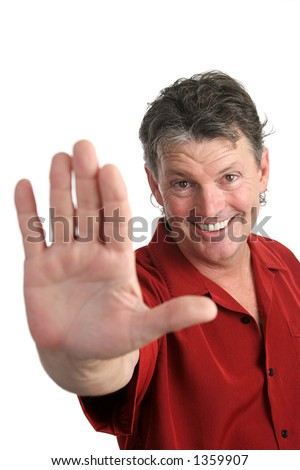 A handsome, casual man holding his hand out in a stop gesture.  Focus on man's face.  Isolated. - stock photo