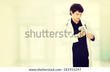 A handsome doctor with money. - stock photo