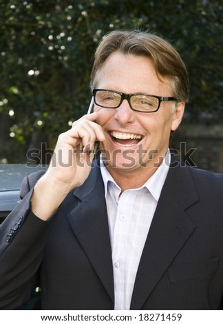 A handsome forties businessman is chatting on his cellphone and laughing - stock photo