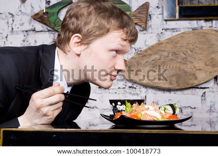 A handsome guy in the restaurant breathes in the scent of sushi - stock photo