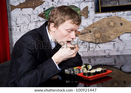 A handsome guy in the restaurant eats sushi - stock photo