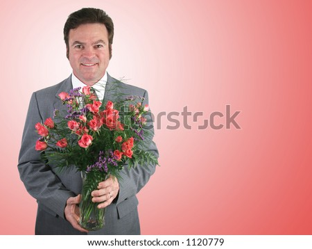 A handsome husband in a suit holding a bouquet of pink sweetheart roses over a pink packground. - stock photo