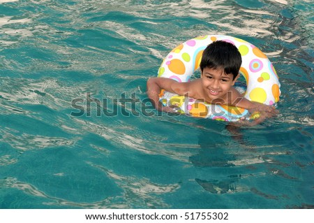 A handsome Indian kid playing in the pool - stock photo