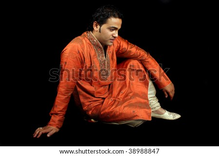 A handsome Indian man in a traditional royal attire in a sad mood, on black studio background. - stock photo