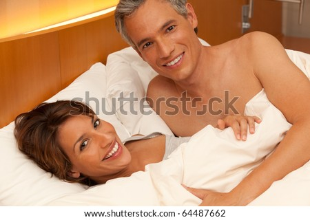A handsome man and beautiful woman smile while laying happily in bed together - stock photo
