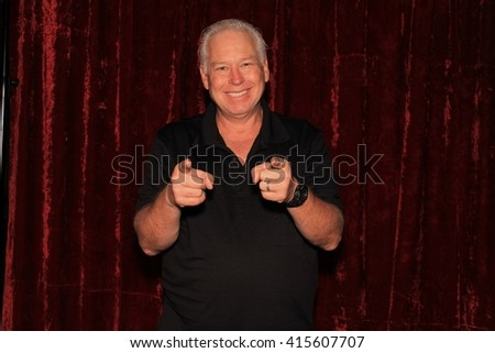 A handsome middle aged man laughs, smiles, and poses with crazy props while he has his pictures taken while in a photo booth. Photo Booths are very popular at all parties and weddings. - stock photo