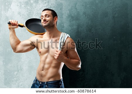 A handsome muscular cook posing with a pan on his shoulder on a textrured backgound with space for text - stock photo