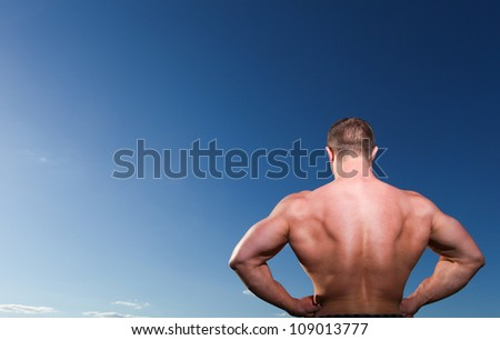 A handsome muscular man standing against the blue sky. Back view - stock photo