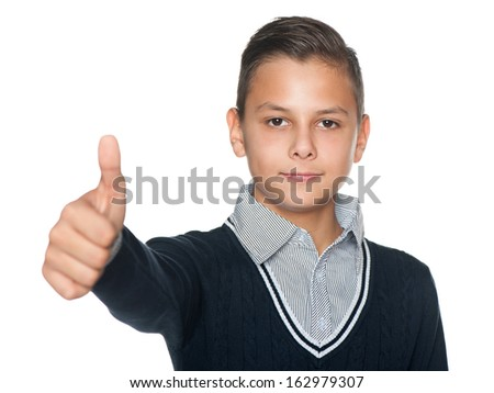 A handsome preteen boy holds his thumb up on the white background - stock photo