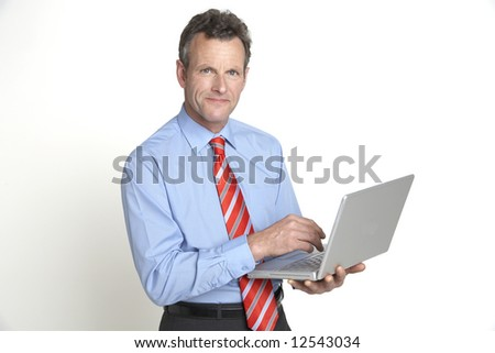 A handsome senior businessman smiles to the camera whilst working on his laptop - stock photo