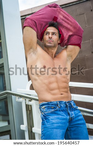 A handsome, sexy, middle age man is taking off his shirt, showing his strong body.  - stock photo