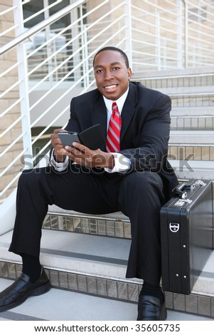 A handsome successful business man on stairs at office with electronic device - stock photo