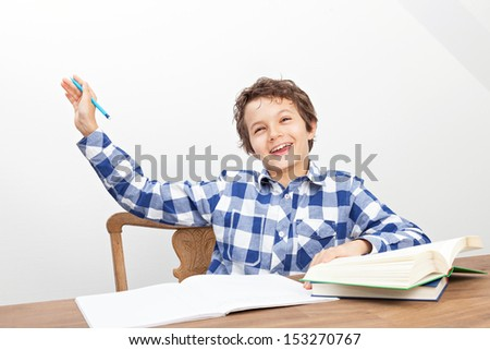 A handsome teenage boy is doing his homework. - stock photo