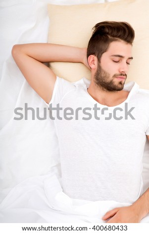 A handsome young adult man sleeping in bed. - stock photo