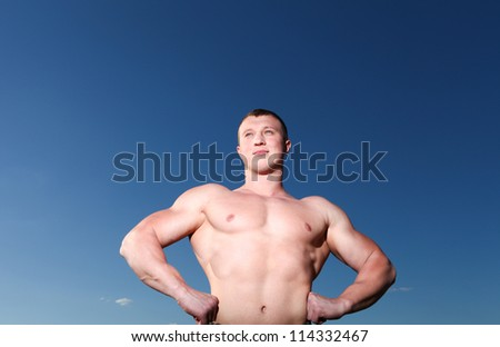 A handsome young athletic and muscular man standing against the blue sky - stock photo