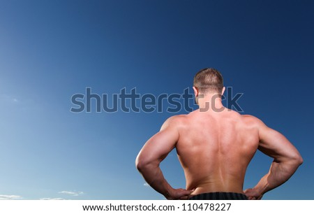 A handsome young athletic and muscular man standing against the blue sky. Back view - stock photo