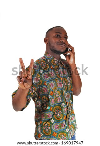 A handsome young black man in a colorful shirt talking on his cell phone for white background.  - stock photo