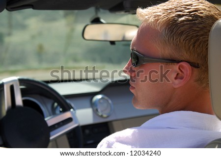 A handsome young blond man driving in the mountains - stock photo