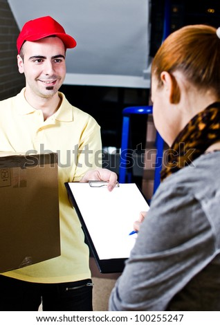 A handsome young courier delivering a package - stock photo