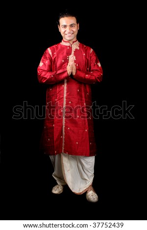 A handsome young Indian guy in a traditional Indian welcome pose, on black studio background. - stock photo