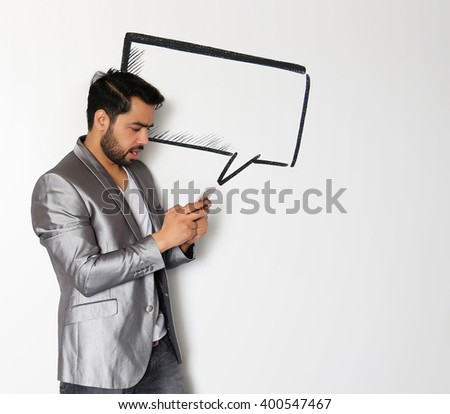 A handsome young Indian man chatting on Smart Phone against a white background - stock photo