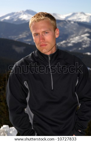 A handsome young man in the snow capped mountains - stock photo
