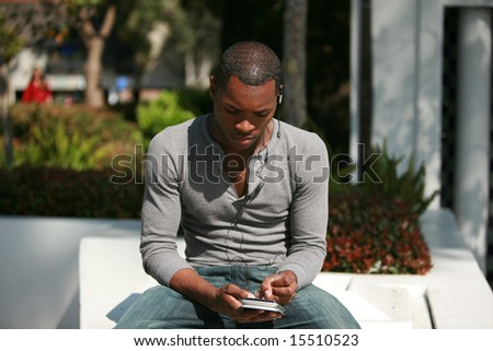 a handsome young man text messages while listening to his mp3 digital music player - stock photo