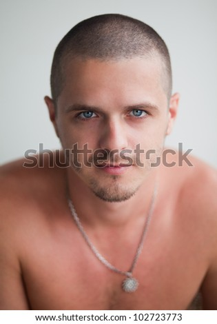 A handsome young man with chainon his neck. Portrait. Grey background - stock photo