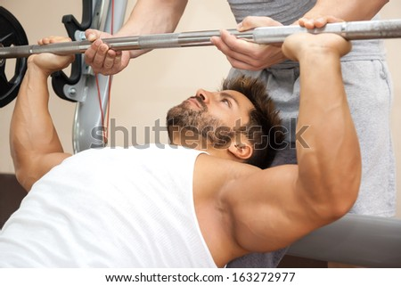 A handsome young muscular sports man doing bench press with a little help - stock photo