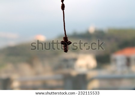 A hanging small knotted rosary with crucifix on a natural background.  - stock photo