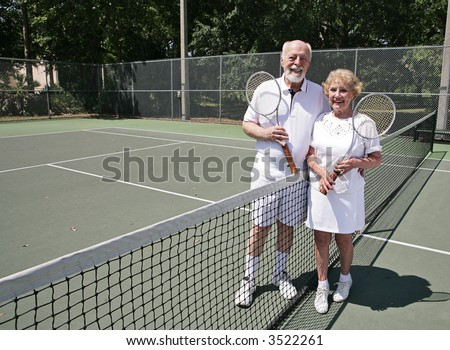 A happy active senior couple on the tennis courts.  Wide view with room for text. - stock photo