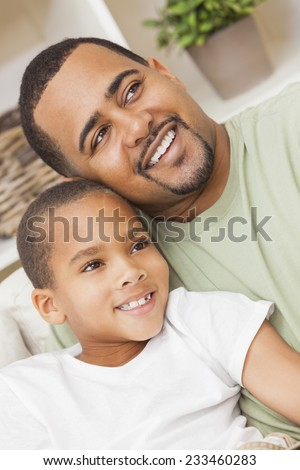 A happy African American man and boy, father and son, family sitting together at home - stock photo