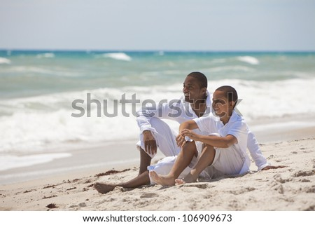 A happy African American man and boy, father and son, family together on a tropical beach in summer sunshine - stock photo