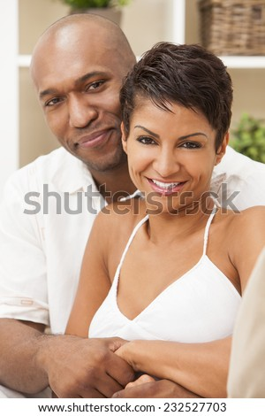 A happy African American man and woman couple in their thirties sitting at home, the woman is in focus in the foreground the man out of focus in the background. - stock photo