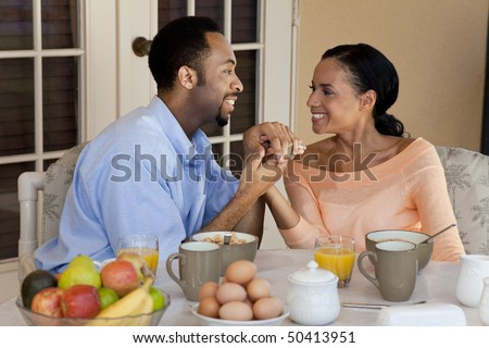 A happy African American man and woman couple in their thirties sitting outside holding hands and having a healthy breakfast - stock photo