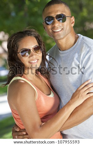 A happy African American man and woman couple in their thirties wearing sunglasses outside together smiling. - stock photo