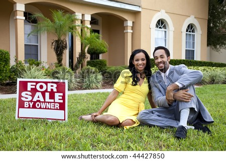 A happy African American man and woman couple outside a large house with a For Sale sign - stock photo