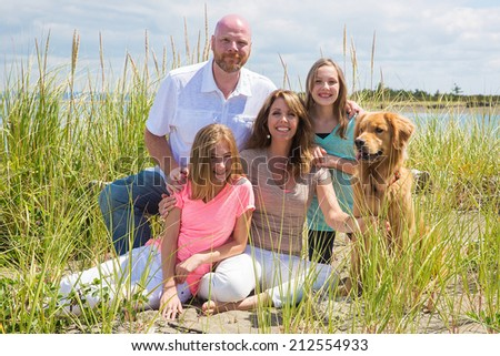 A happy American family on vacation at the beach with their golden retriever dog - stock photo