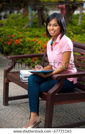 A happy and attractive college student smiles and writes into her notepad.  20s female Asian Thai model of Chinese descent. - stock photo